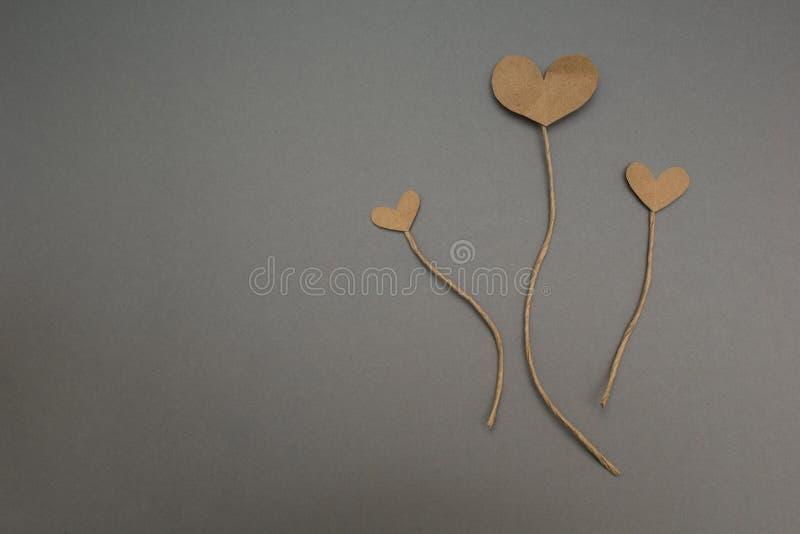 Pappers- hjärtor, som blommor på grå bakgrund royaltyfria bilder