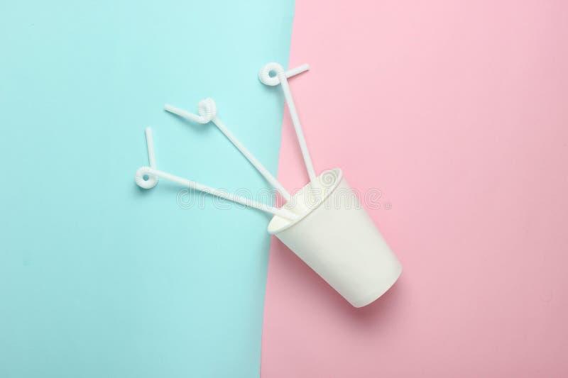 Pappers- kaffekopp med coctailsugrör på en kulör pastellfärgad bakgrund, bästa sikt, minimalism royaltyfria foton