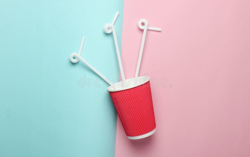 Pappers- kaffekopp med coctailsugrör på en kulör pastellfärgad bakgrund, bästa sikt, minimalism fotografering för bildbyråer