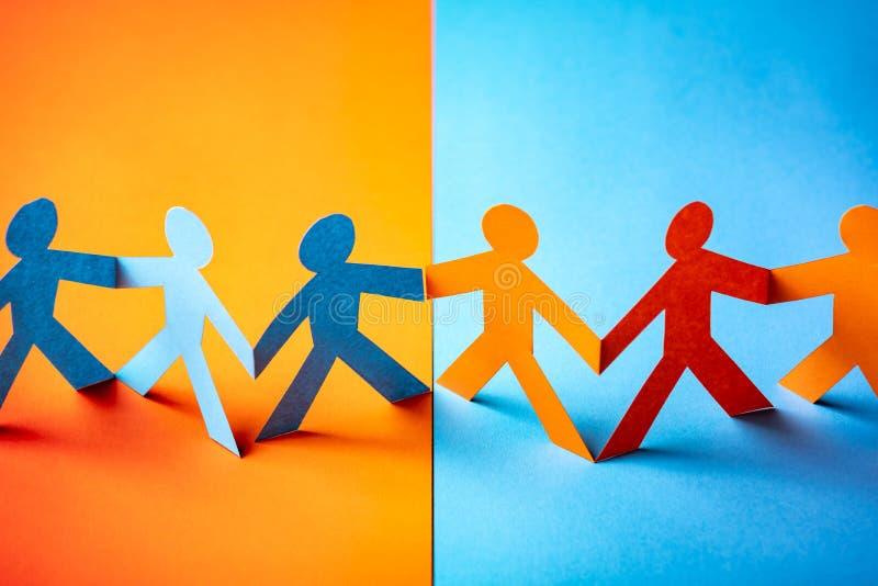 Pappers- klippt begrepp - mångkulturellt samarbete av de två grupperna arkivfoton
