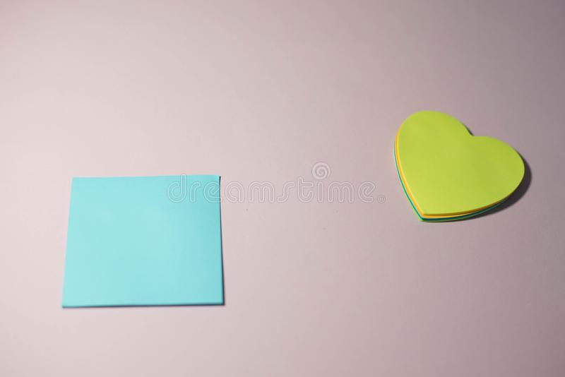 Pappers- klisterm?rkear p? en rosa bakgrund royaltyfri bild