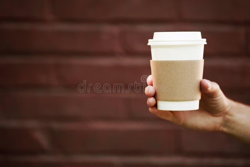 Pappers- kopp av takeaway kaffe i handen royaltyfria bilder