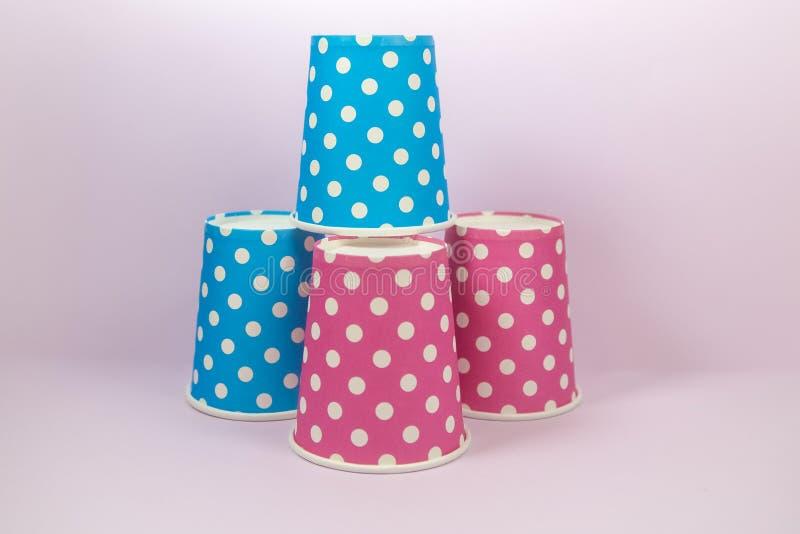 Pappers- kopp för blå och rosa prick på den rosa bakgrunden royaltyfri foto