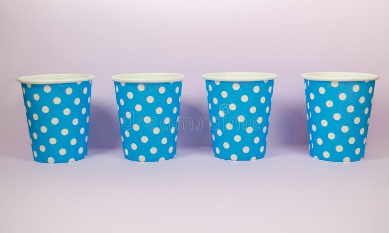 Pappers- kopp för blå prick på den rosa bakgrunden royaltyfria foton