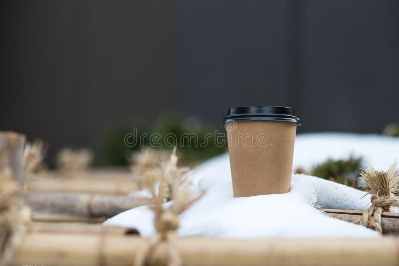 Pappers- kopp för kaffe i snö royaltyfria foton