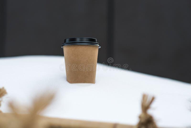 Pappers- kopp för kaffe i snö arkivfoto