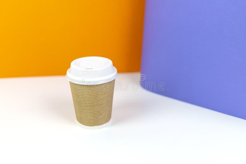 Pappers- kopp för kaffe med färgrik bakgrund fotografering för bildbyråer