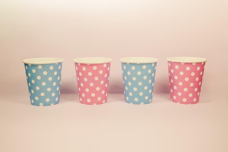 Pappers- kopp för rosa färg- och blåttprick på den rosa bakgrunden arkivbilder