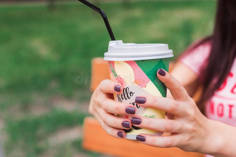 Pappers- kopp kaffe i händerna av en flicka royaltyfria bilder