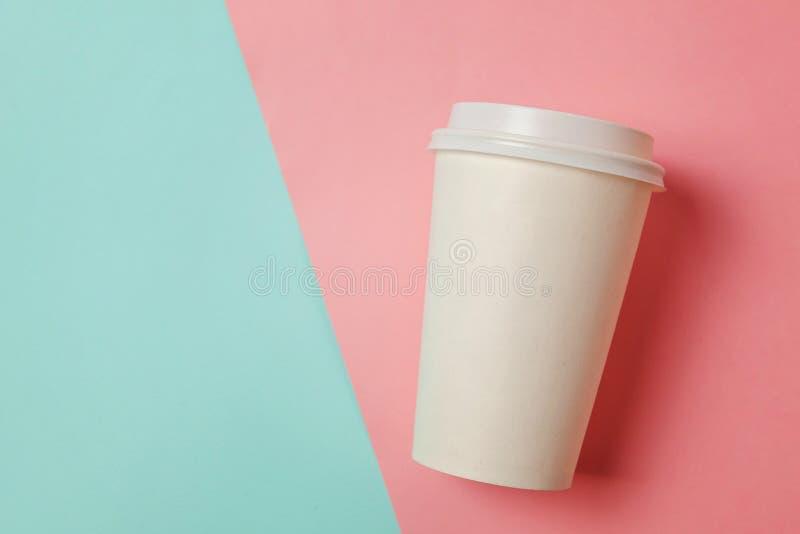 Pappers- kopp kaffe på blå och rosa bakgrund arkivbilder