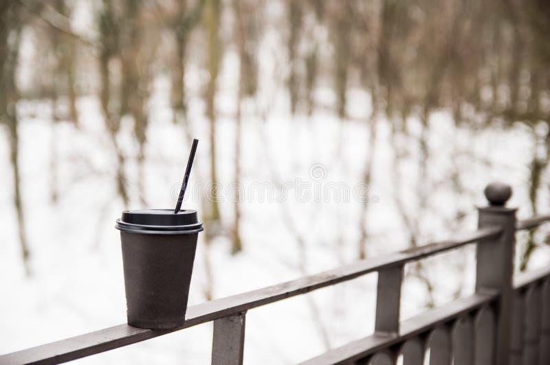 Pappers- kopp med kaffest?llningar p? en metallledst?ng p? bron arkivbilder