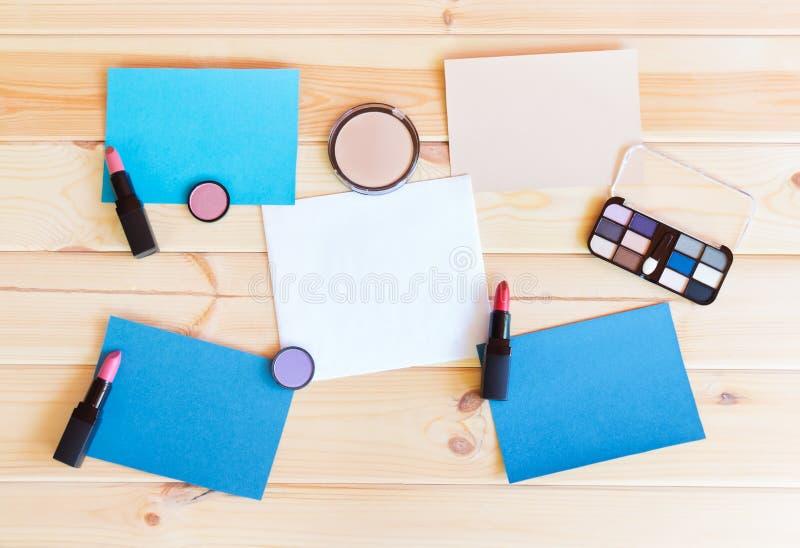 Pappers- kort och makeupskönhetsmedel royaltyfria foton