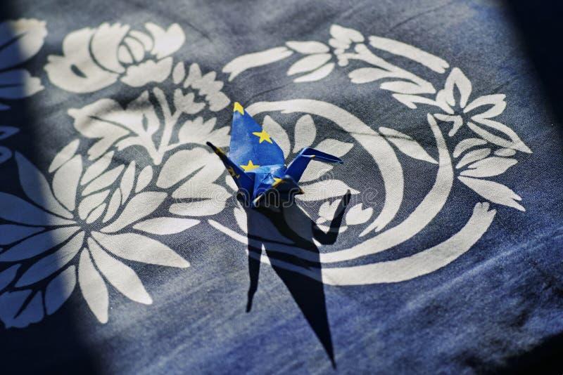 Pappers- kran på den handwoven torkduken royaltyfri foto