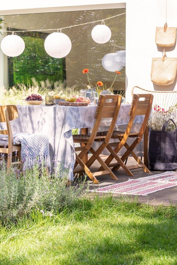 Pappers- lampor på en terrass med en tabell och stolar bredvid en gräsmatta Verkligt foto arkivbilder