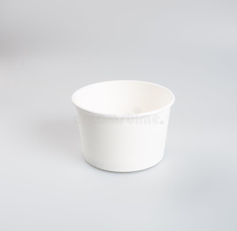Pappers- matbehållare eller kopp på en bakgrund arkivbild