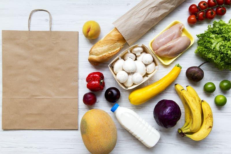 Pappers- påse av vård- råkost på vit träbakgrund Matlagningmatbakgrund Lägenhet-lekmanna- av nya frukter, veggies, gräsplaner, få arkivbilder