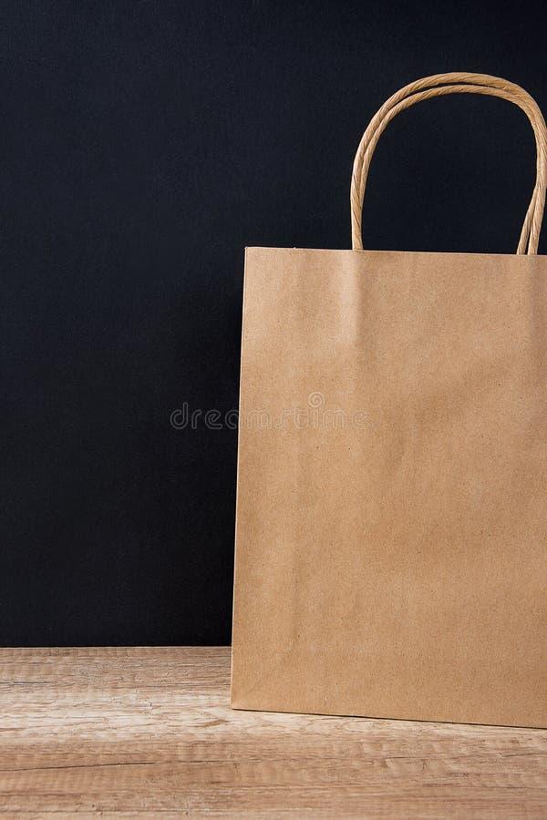 Pappers- påse för tomt brunt hantverk på svart bakgrund Försäljningsrabattshopping Black Friday Cyber måndag white för julgåvaiso royaltyfri bild