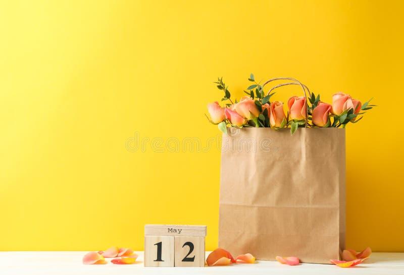 Pappers- påse med buketten av orange rosor och kalendern på den vita tabellen mot färgbakgrund arkivfoto