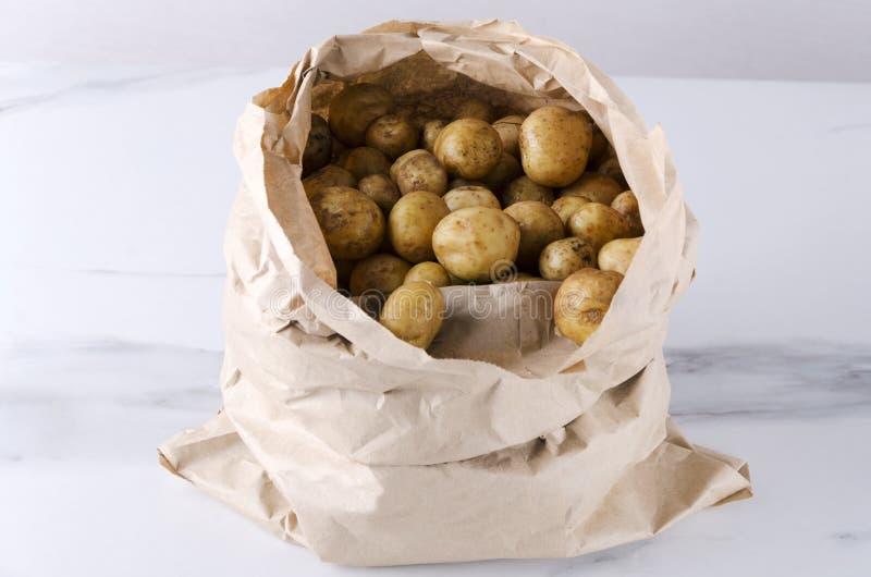 Pappers- påse mycket av nya potatisar för okokt vår på den vita tabellen arkivbild