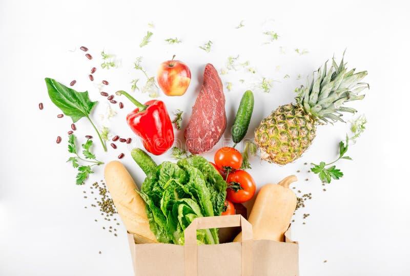Pappers- påse mycket av sund mat på en vit bakgrund royaltyfria bilder