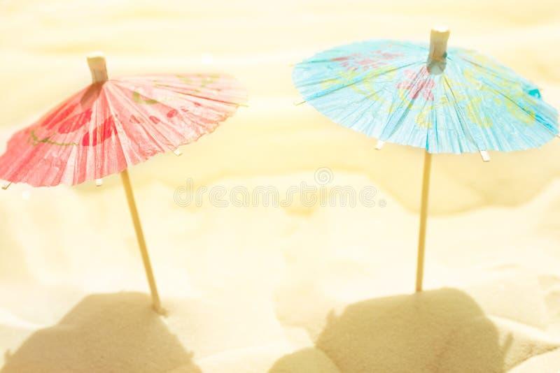 Pappers- paraplyer för coctail på strandsand i guld- solljus Idérik konstnärlig stiliserad bild Avkoppling för sommarsjösidasemes royaltyfri bild