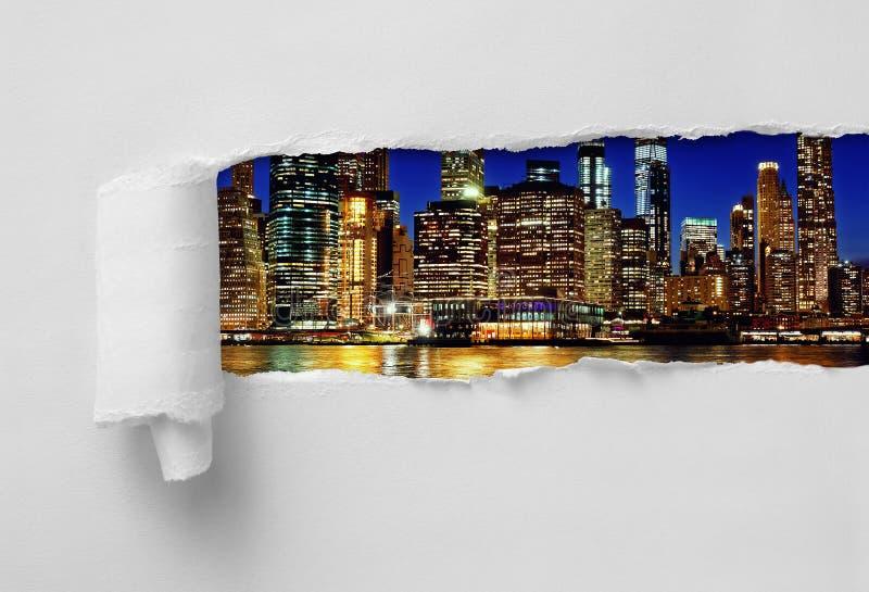 Pappers- Ripped som avslöjer Manhattan New York City på natten royaltyfri fotografi
