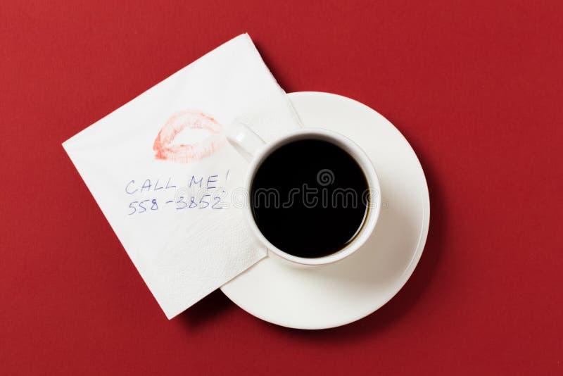 Pappers- servett med en kyss- och kaffekopp på röd bakgrund arkivfoto