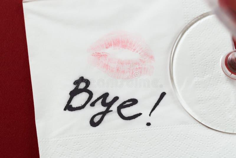 Pappers- servett med en kyss och en vinglas på röd bakgrund royaltyfria foton
