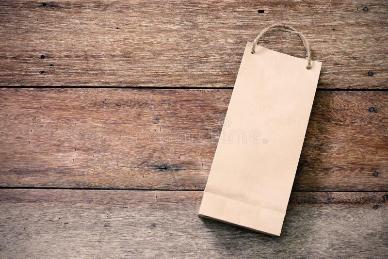 Pappers- shoppingpåse på trä royaltyfria foton