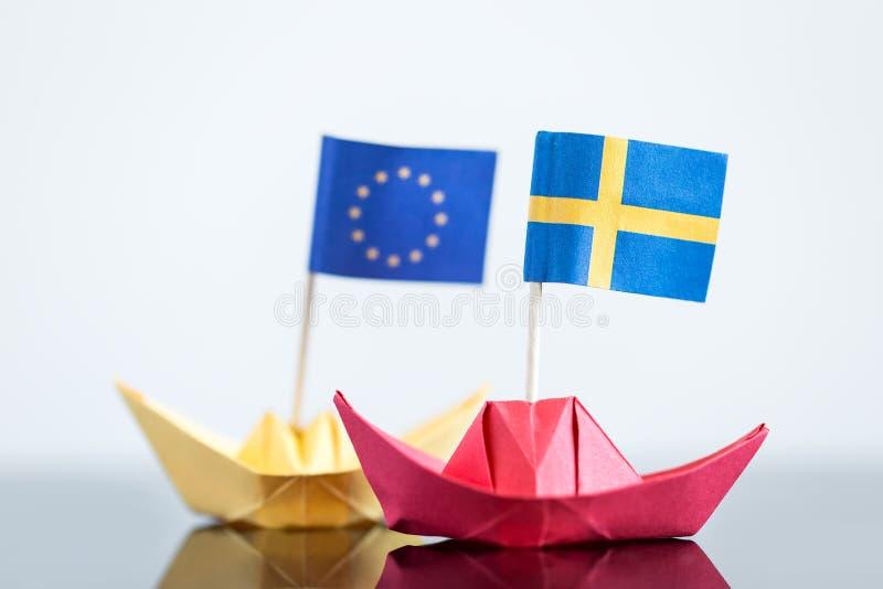 Pappers- skepp med svensk och den europeiska flaggan royaltyfria bilder