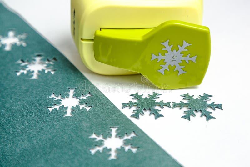 Pappers- snöflingor med hålstansmaskin royaltyfria bilder