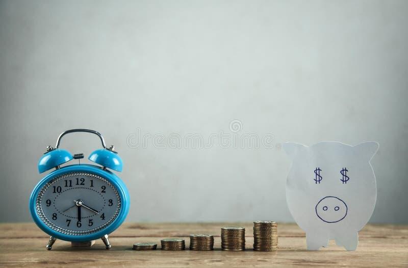 Pappers- spargris, bunt av mynt och ringklocka på trätabellen Tid som investerar dina besparingar arkivfoton