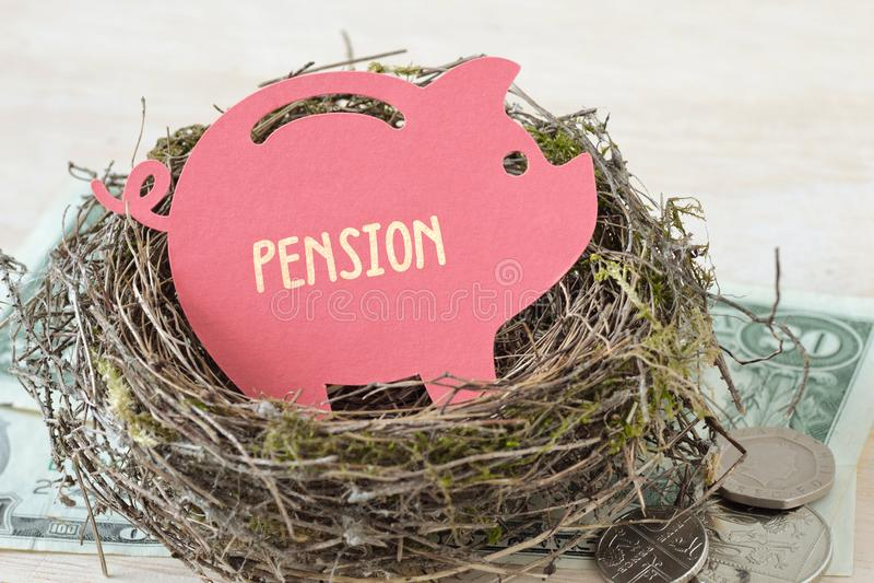 Pappers- spargris med ordpensionen i rede på pengar - begrepp av pensionsfonden arkivfoton