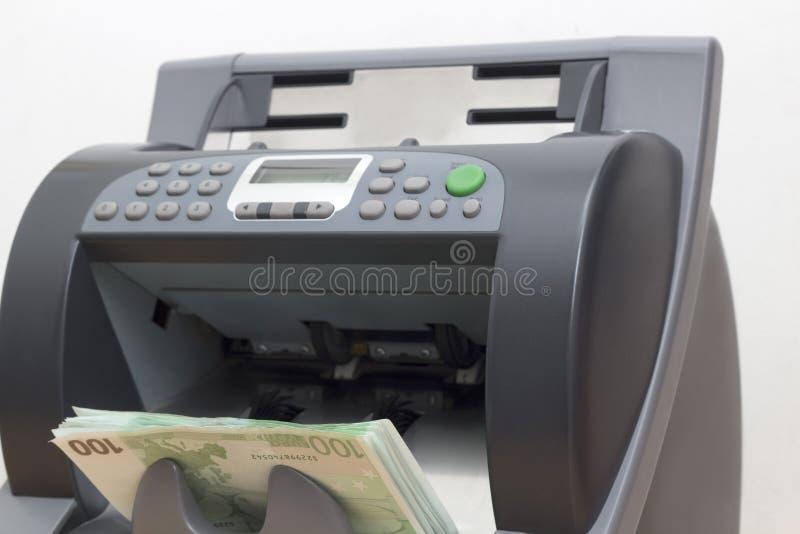 Pappers- valuta i pengarna som räknar maskinen royaltyfri fotografi