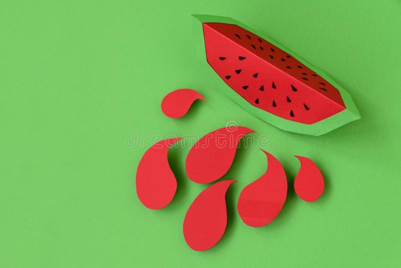Pappers- vattenmelonskiva med färgstänk på grön pastellfärgad bakgrund idérik idé Konstmatbegrepp arkivbild