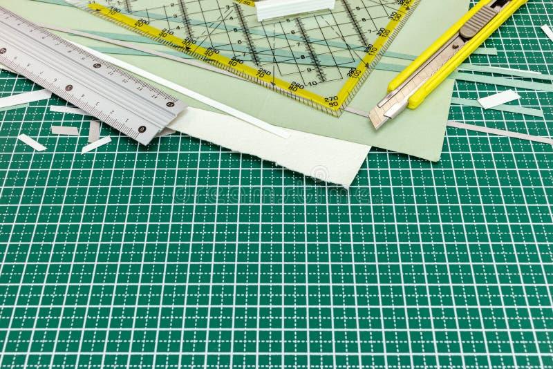Pappersark med metalllinjalen och den nytto- kniven på grönt klipp royaltyfri fotografi