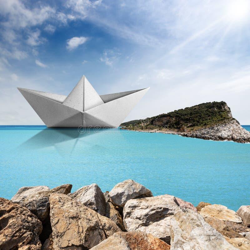 Pappersbåt i ett turkoshav med öar och himmel med moln arkivbild