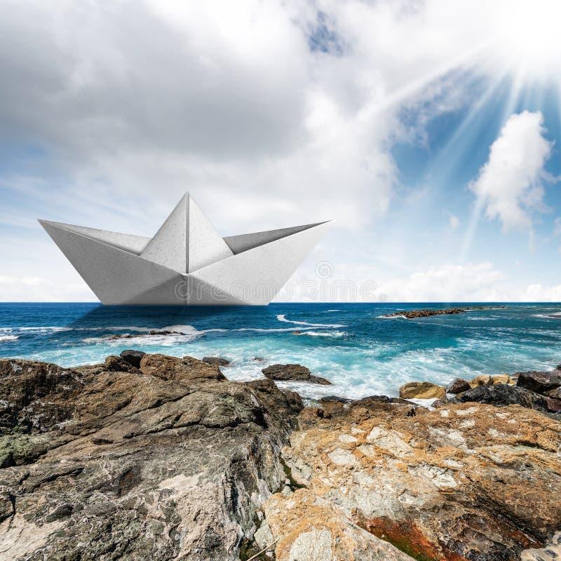 Pappersbåt i havet med klippor och himmel med moln royaltyfria bilder