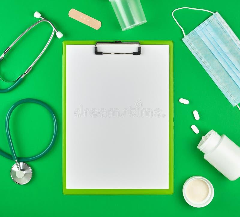 pappershållaren med tomma vita ark, den medicinska stetoskopet, piller och textilen förbinder royaltyfri fotografi