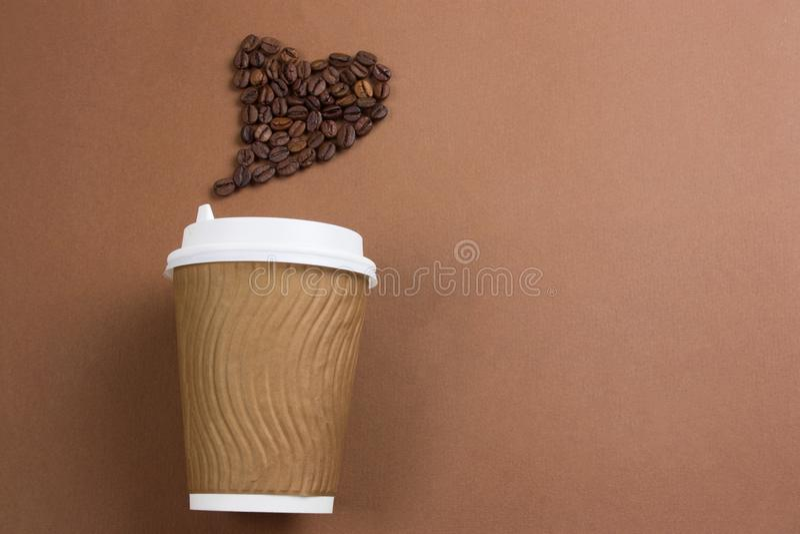 Papperskaffe som går kopp och hjärta som göras från kaffebönor, kopieringsutrymme, brun bakgrund arkivfoto