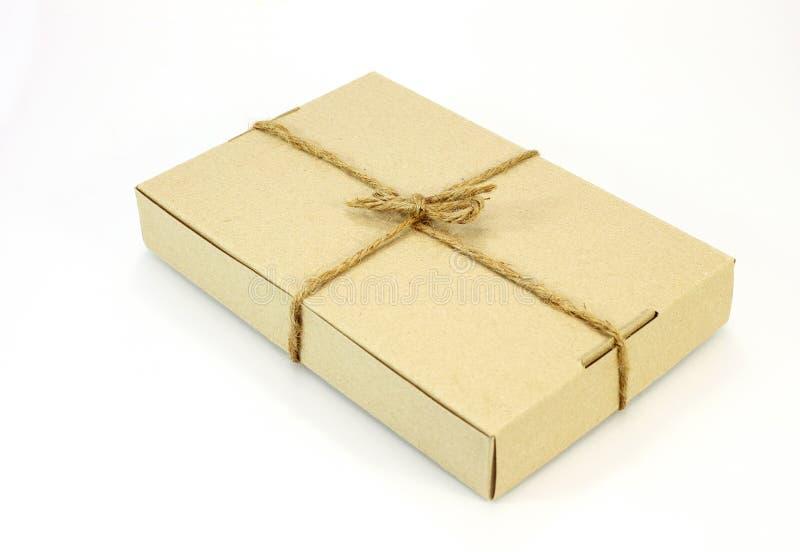 Papplåda som slås in med brunt papper och binds med kabel royaltyfri bild