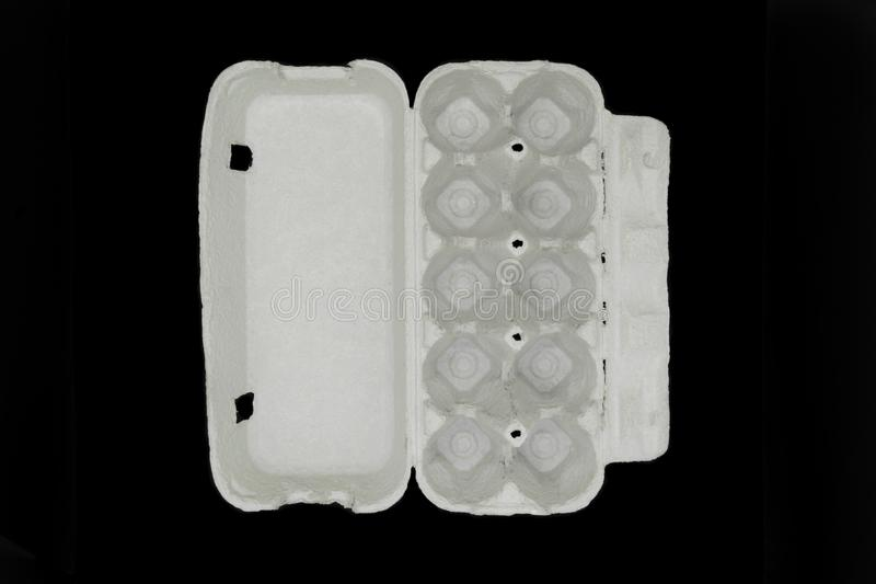 Pappleerer Behälter für zehn Stückeier lokalisiert auf schwarzem Hintergrund lizenzfreies stockbild