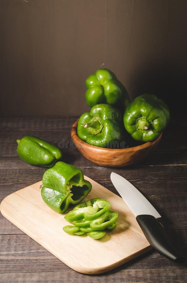paprica del peperone verde in una ciotola di legno e taglio su una paprica peperone verde/del bordo di legno in una ciotola di le immagini stock libere da diritti