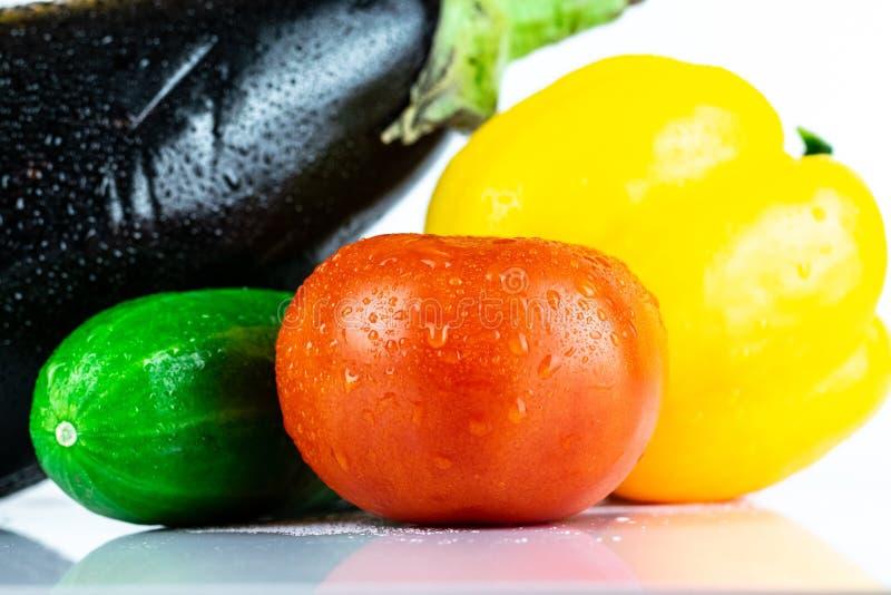 Paprica, melanzana, pomodoro, cetriolo isolato sulla lavagna bianca Verdure organiche Concetto sano di cibo immagine stock