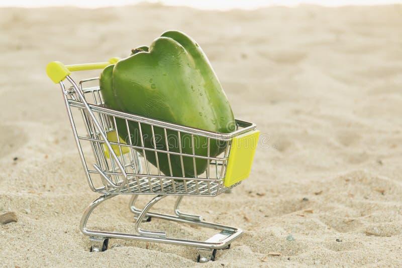 Paprica verde del peperone dolce nello standingon di compera del carrello la sabbia Peperone dolce verde sul carretto per vendita immagine stock