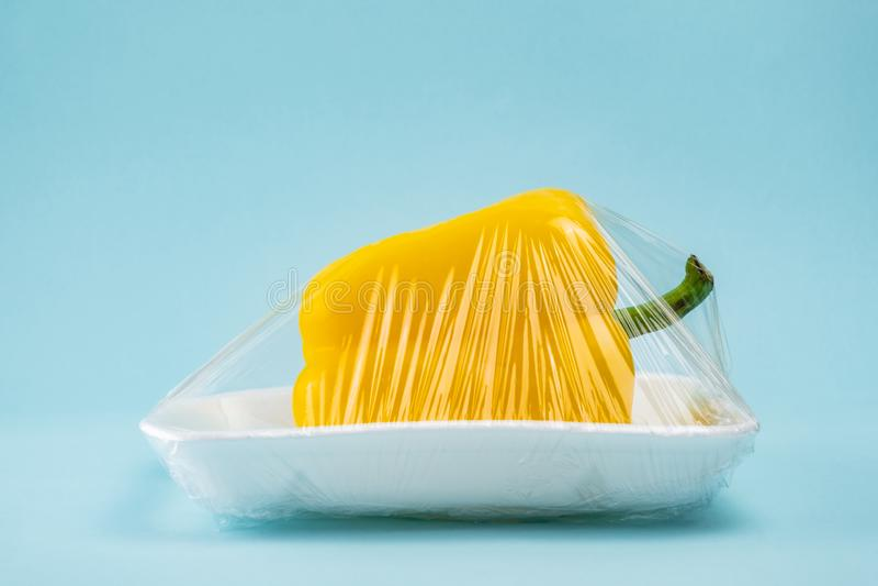 Paprika amarillo envuelto en clingfilm plástico en fondo azul foto de archivo