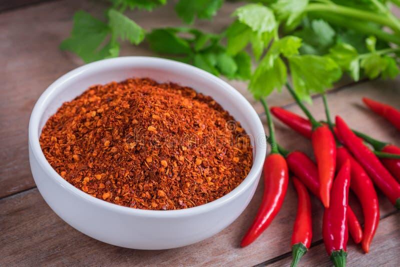 Paprika Cayennepfeffer in der Schüssel und frischer Paprika auf Holztisch stockbild