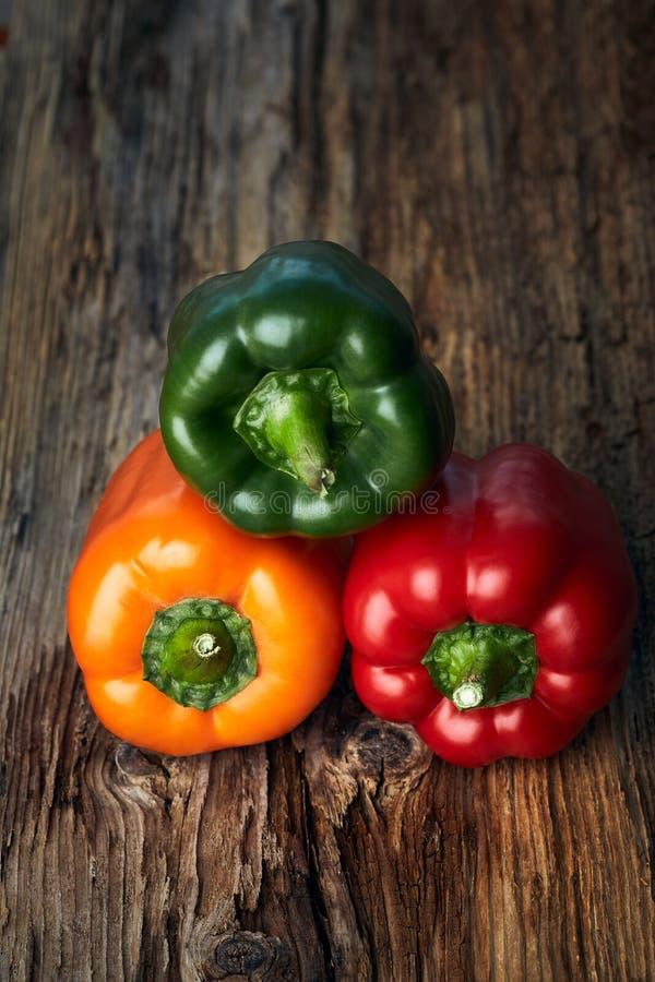 Paprika colorida de las pimientas verdes, amarillas, y rojas en fondo imagenes de archivo