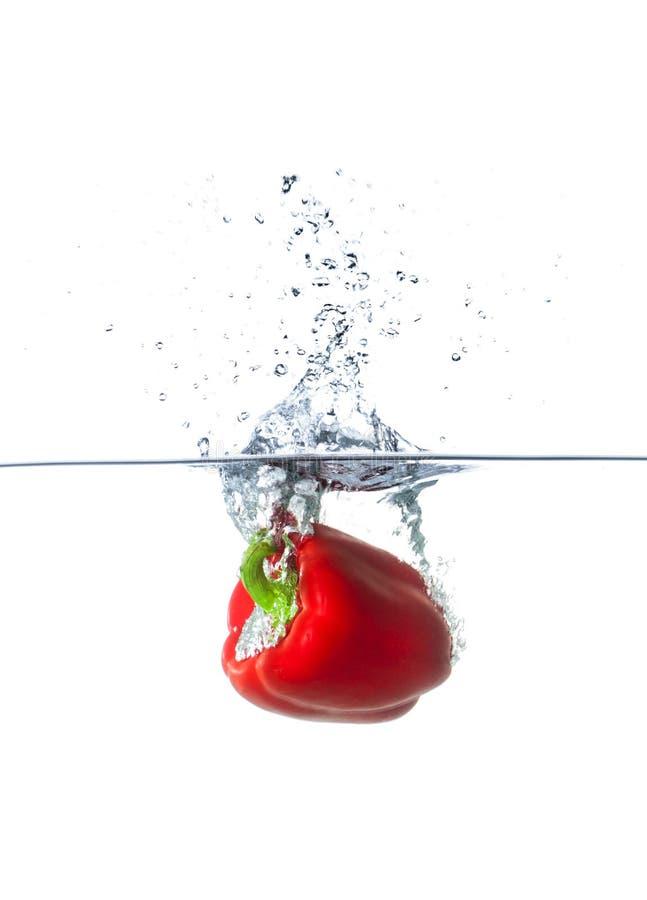 Paprika Falling roja fresca en agua imagenes de archivo