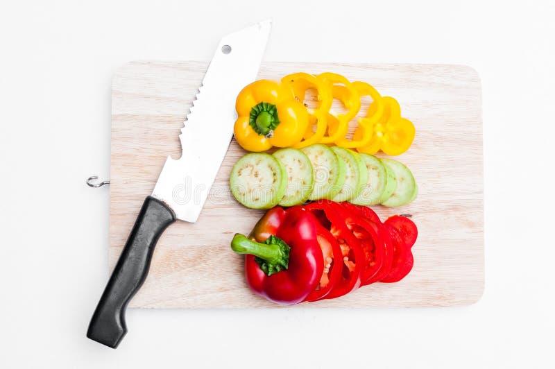 Paprika frais jaune et rouge découpé en tranches sur le conseil en bois images stock